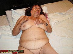 Busty older latina lady is resting on a bed