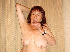 Red-haired mature makes striptease pics